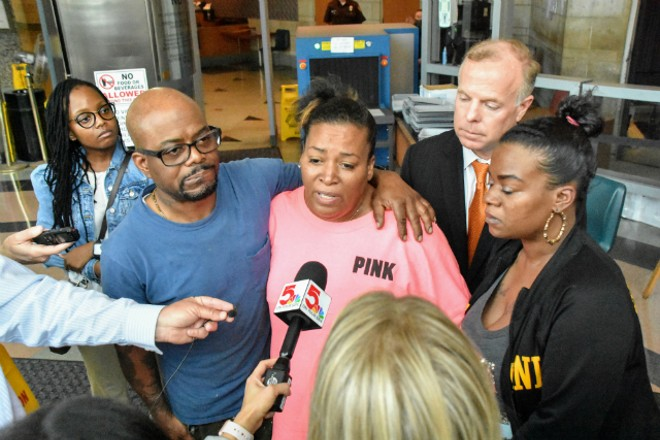 Robert Hall (left) and Karen Carter (center) talk to reporters after a Ladue officer was charged for shooting their daughter. - DOYLE MURPHY