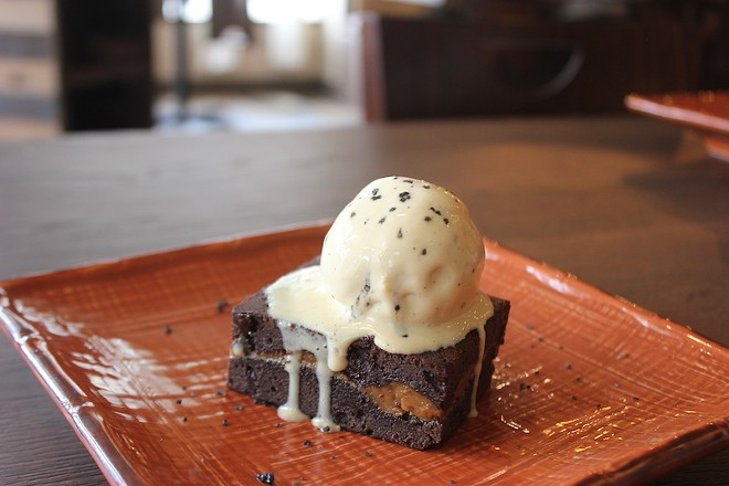 A brownie has a caramel layer and comes topped with a scoop of ice cream. - SARAH FENSKE