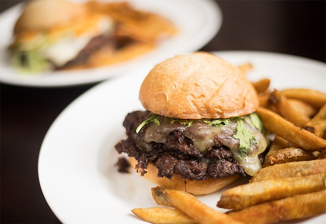 """The three-stack burger is topped with micro arugula and """"Carmeo"""" onions and smothered in raclette cheese. - MABEL SUEN"""