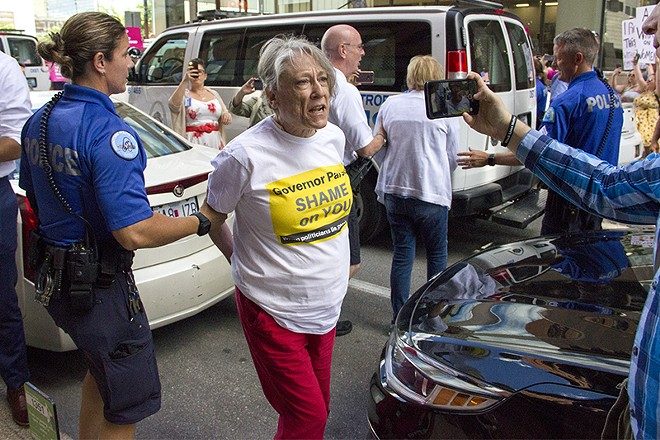 Police lead away a protester on Thursday, May 30, after a sit-in at the Wainwright building. - DANNY WICENTOWSKI