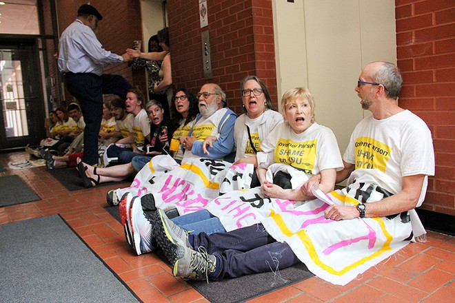 A state employee steps over a line of protesters blocking the elevators in the Wainwright Building. - DANNY WICENTOWSKI
