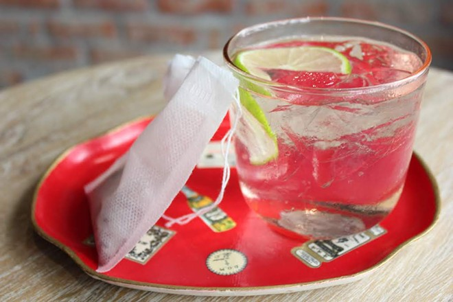 """One of the cocktails served at Indo is the """"Plastic Chair in the Rose Garden,"""" a gin drink with a bag of rock candy and hibiscus. - KATIE COUNTS"""