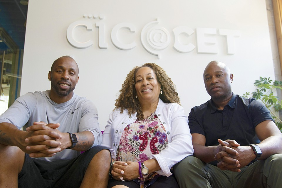 REAL Cannabis Co.'s Justin Gage, left, and Cheryl Watkins-Moore, center, with the company's founder and president Derek Mays.