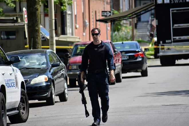 An officer leaves the scene of a five-hour standoff in Tower Grove South. - DOYLE MURPHY