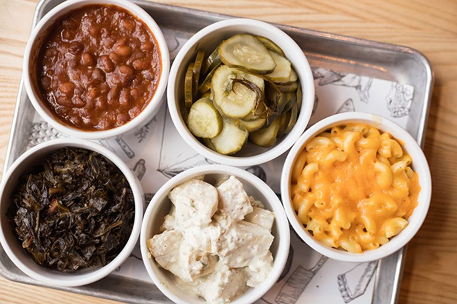 A selection of sides: pit beans, fresh dill pickles, mac 'n' cheese, candied bacon-jalapeno potato salad, ham hocks with collard greens. - MABEL SUEN