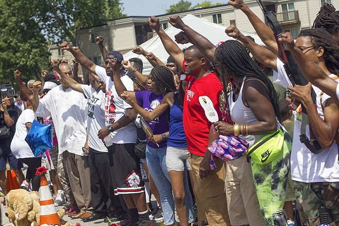 """A group of """"front line"""" Ferguson protesters, including Cori Bush (center, in purple t-shirt) raise their fists in recognition during Brown's memorial ceremony. - DANNY WICENTOWSKI"""