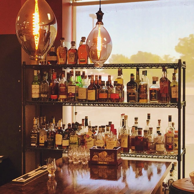 Whiskey, scotch, bourbon, rye and more line the shelves at (IN)Famous Bar inside The Wine & Cheese Place in Clayton. - VIJAY SHROFF