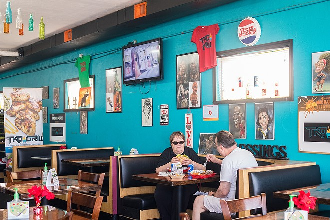 The dining area at TKO Grill features artwork of celebrities and famous boxers. - MABEL SUEN