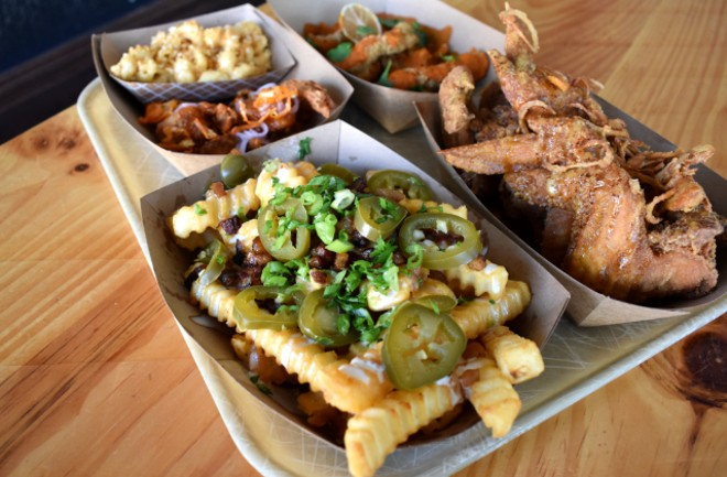 Large loaded crinkle-cut fries with Magic Seasoning, beer queso, house-cured bacon bits, house pickled jalapeños and green onion. - LIZ MILLER