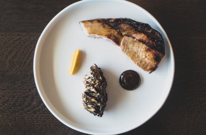 Grilled black bass with biquino peppers, lobster mushrooms and bonito butter. - COURTESY CINDER HOUSE AT FOUR SEASONS ST. LOUIS