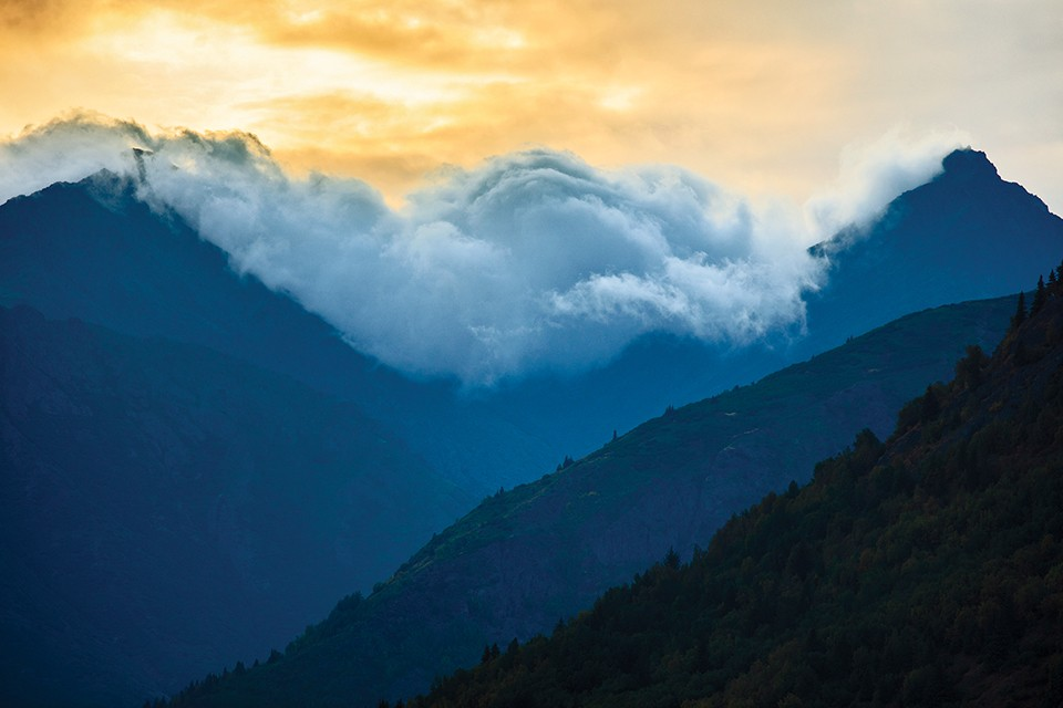 Clouds crash and pour over the ridges of Alaska's Kenai Peninsula. - JOSHUA ROWAN