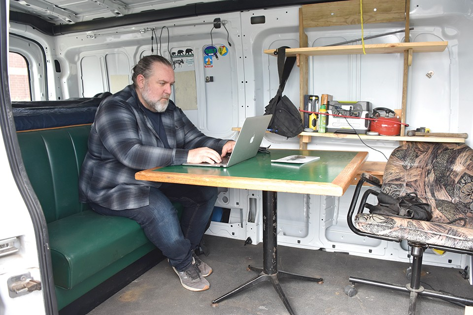Joshua Rowan's home office away from home: a rugged and well-traveled Ford van. - DOYLE MURPHY