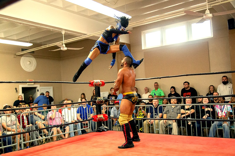 Clad in a white and blue lucha libre mask, Seishin delivers a flying kick to Hakim Zane. - MONICA MILEUR