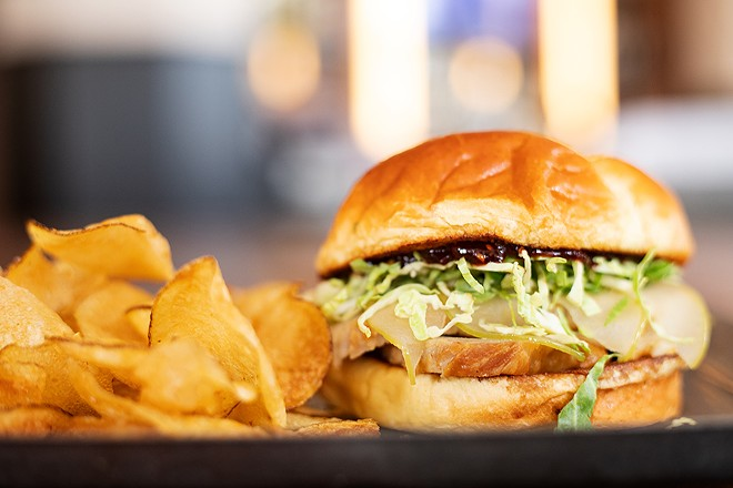 A pork chop sandwich pairs thick slices of the meat with a tart raspberry barbecue sauce, pickled green apples and shaved Brussels sprouts, all tucked into a pillow-soft bun. - MABEL SUEN
