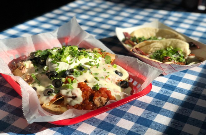 Pulled pork nachos topped with queso, sour cream, Esther's beans, black olives and green onions. - LIZ MILLER