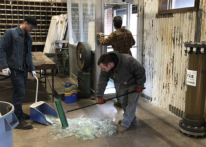 Refab workers clean up glass from a Monday morning break-in. - COURTESY OF ERIC SCHWARZ