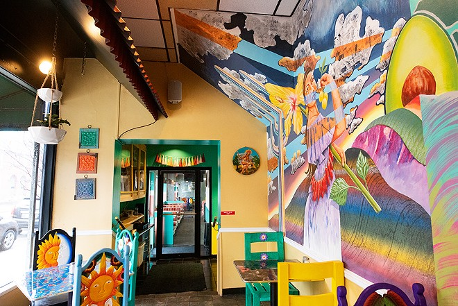 The colorful walls provide a sunny backdrop for even more colorful artwork — photographs, paintings and a beautiful mural depicting two traditionally-dressed Mexican women surrounded by flowers, fruits and vegetables. - MABEL SUEN