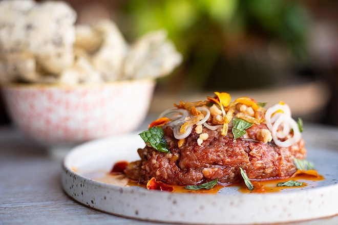 Spicy lamb tartare topped with fried shallots and candied pine nuts and served with a rice cracker. - MABEL SUEN