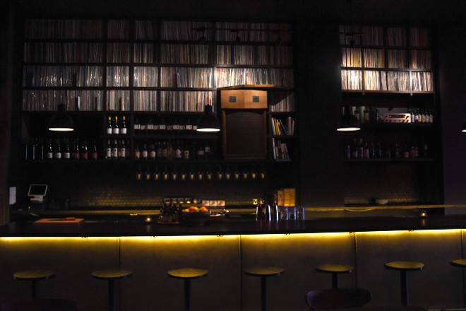 The bar is lined with shelves brimming with vinyl records. - TRENTON ALMGREN-DAVIS