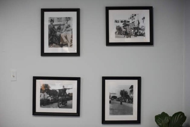 Photos of Trinh's dad performing motorcycle stunts from his time in the circus hang on the wall. - TRENTON ALMGREN-DAVIS