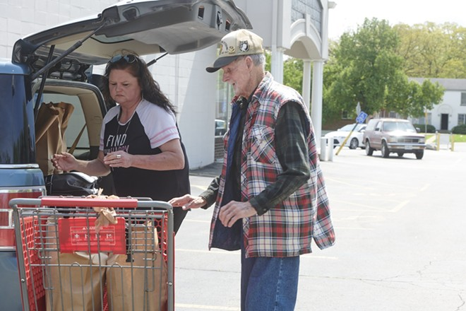 Caregiver Denise Phelps helps her 85-year-old uncle, William Speck, with groceries  from Feed My People  on April 24 in Lemay. - MARY BUTKUS