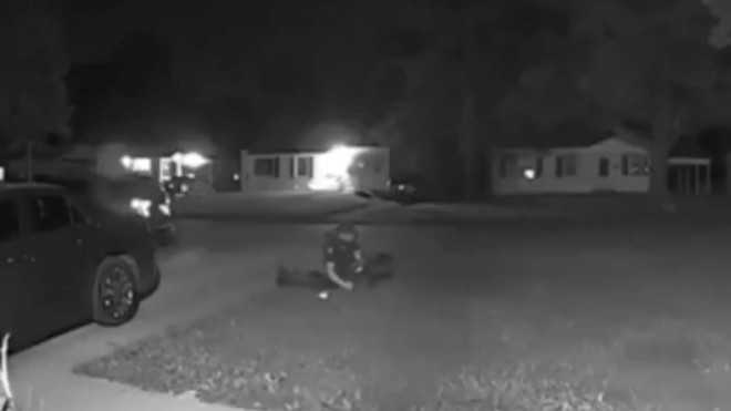 A Florissant police officer, shown in still image of a video first aired by Real Stl News, sits on top of a man after hitting him with his car. - SCREENGRAB