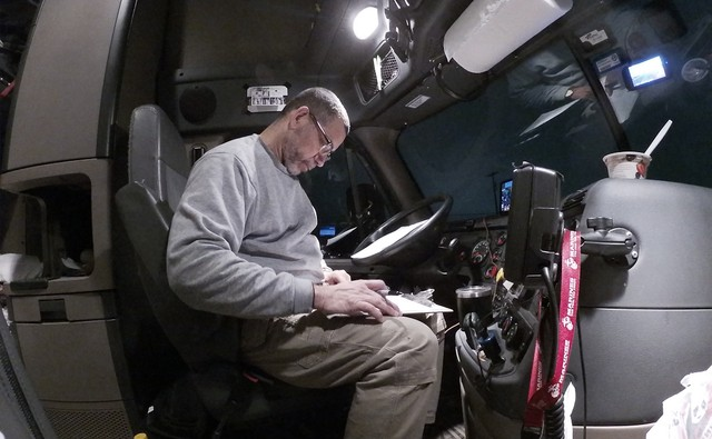 Long-haul truck driver Chet Gordon completes his load paperwork at 6:20 a.m. after a 3:30 a.m. Tyson meats load delivery to the Walmart Distribution Center in Pottsville, Pennsylvania, on March 17.