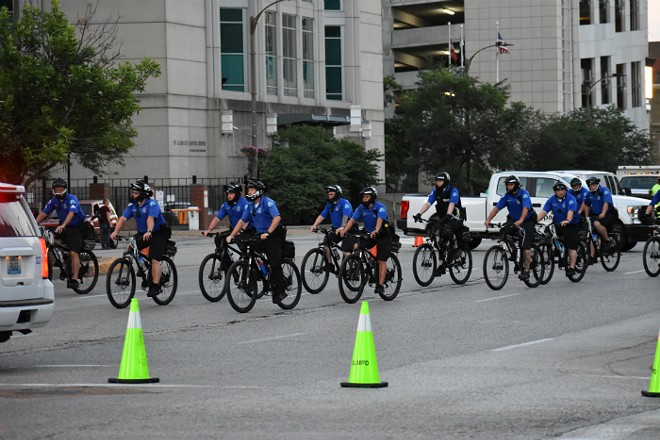 Bicycle police pedal away from City Hall. - DOYLE MURPHY