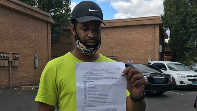 Terrell Porter is holding the letter his wife Janica Washington received from Sansone Group, the owner of Southwest Crossing apartments. The letter informed the couple they had violated tenant rules because of what she said in an RFT story published in August. - MIKE FITZGERALD