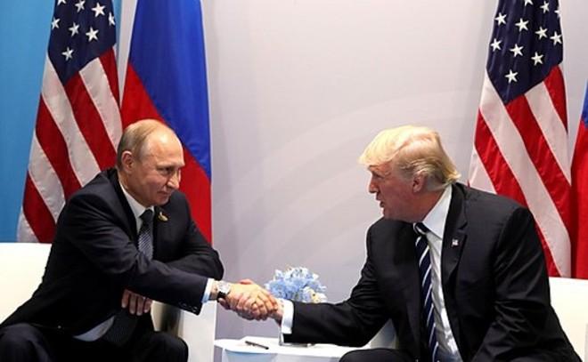 Vladmir Putin and Donald Trump shake hands in 2017. - WIKIMEDIA COMMONS