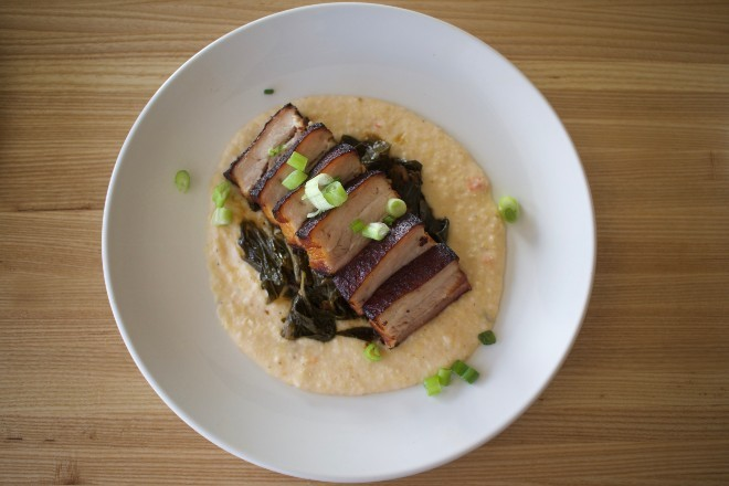 Crispy pork belly is served over grits with collard greens. - CHERYL BAEHR