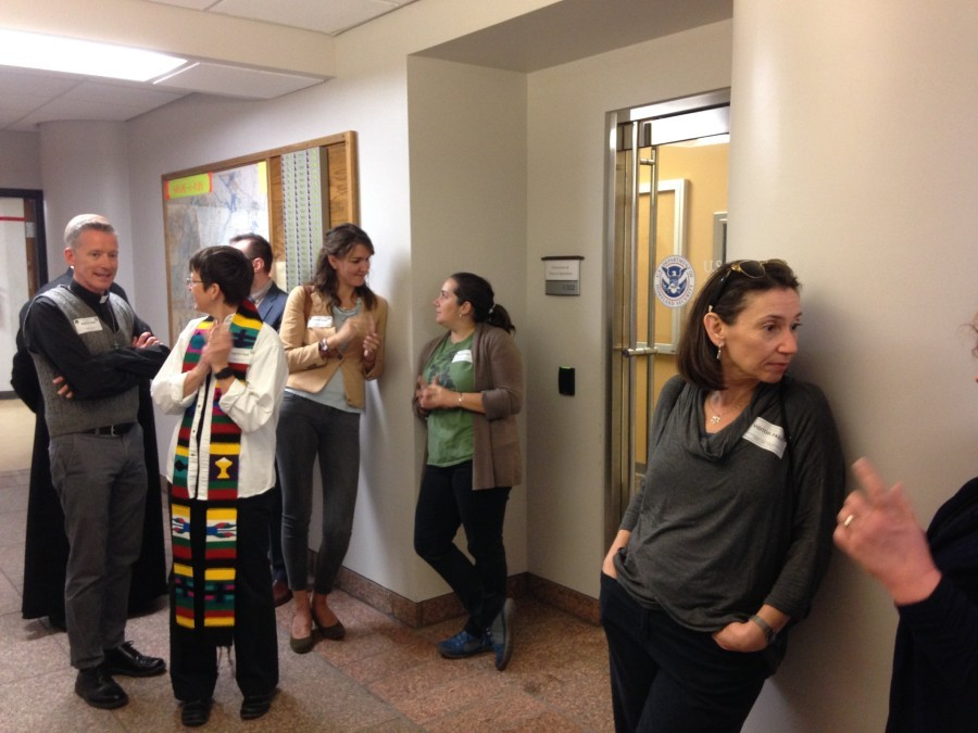 Nicole Cortés and Sara John (green shirt) talk outside the door of the ICE office in St. Louis. - DOYLE MURPHY