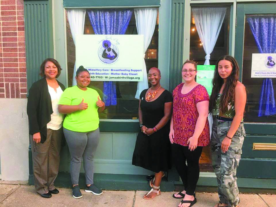 Tru Kellman, center, in front of Jamaa's first home with (from left) Yvonne Smith, Noni Rogers Boyd, Haley Manning and Madyson Winn.