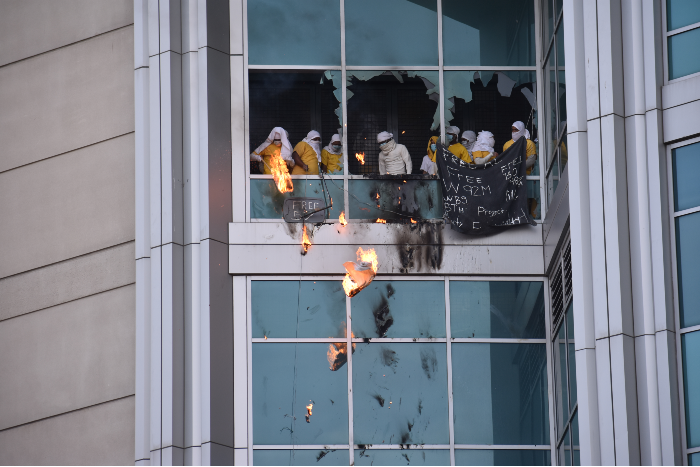 Inmates drop flaming debris from the windows. - DOYLE MURPHY