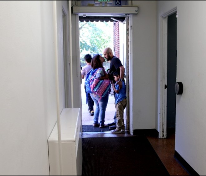 Alex Garcia kisses Carly goodbye while their son Xander clings to his leg at the door of Christ Church in the new film, The Garcia Family. - MISSION MAN MEDIA
