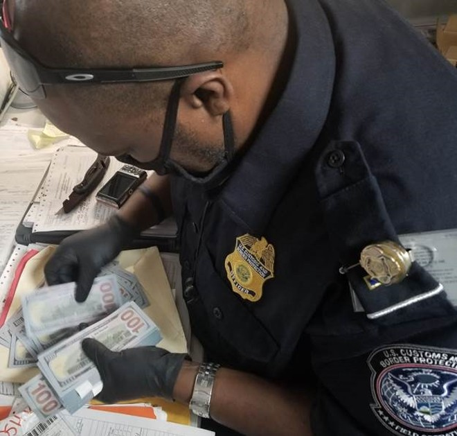 A customs agent counts a stack of fake $100 dollar bills. - U.S. CUSTOMS AND BORDER PROTECTION