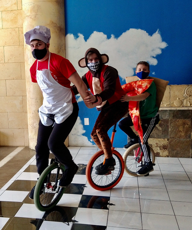 A chef, a monkey and a slice of pizza ride unicycles for their St. Louis thin-crust pizza recipe. - CIRCUS HARMONY