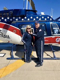 Tom Becker, a pilot with Air Evac Lifeteam in Missouri, awards flight wings in 2019 to Trisha Dutt, a nurse, after she had helped 50 patients on helicopter rescues. - HEATHER STEPHENS