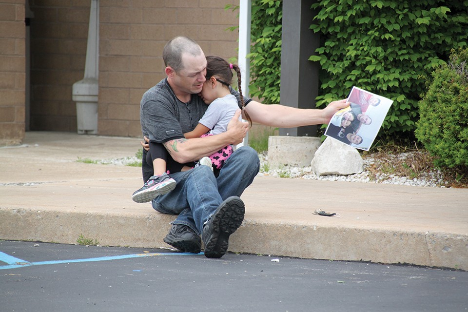 Days after an immigration judge ordered Dow's deportation in 2014, Justin Boyer comforts the couple's young daughter outside a Troy, Missouri jail. - RENEE BRONAUGH/PARK HILLS DAILY JOURNAL