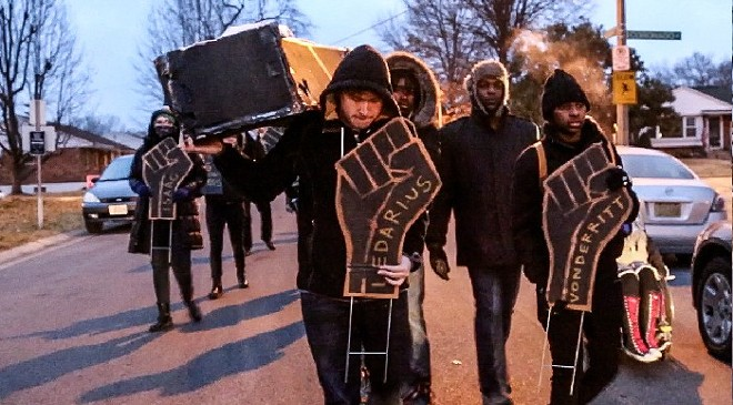 """Activists led a """"funeral march"""" down Mayor Francis Slay's street in South St. Louis early on the morning of Feb. 9, 2015, and left a cardboard coffin on his doorstep. They also stuck signs in his yard with the names of those recently shot and killed by St. Louis city police, along with another sign that said, """"They tried to bury us but didn't know we are seeds."""" Among their demands for Slay was passage of the civilian oversight legislation. See a video of the protest. - REBECCA RIVAS/MISSOURI INDEPENDENT"""
