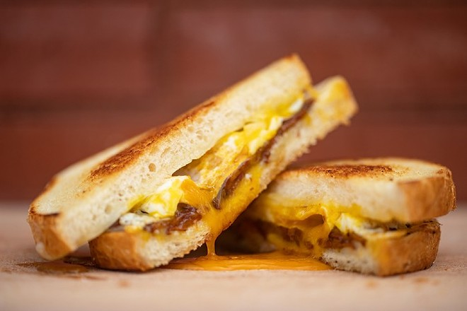The Combo with three slices of aged white cheddar on toasted sourdough with three slices of applewood-smoked bacon and a fried egg, finished with sea salt and honey. - MABEL SUEN