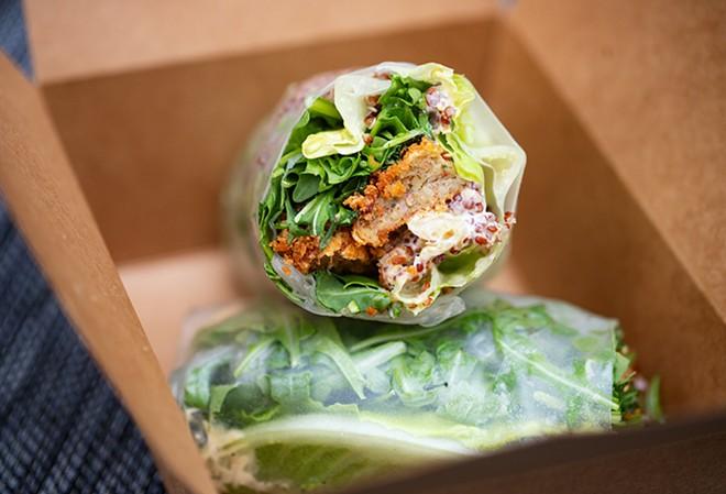 Basil crab cake served in a rice paper wrap with baby arugula, garlic-basil aioli and Sriracha. - MABEL SUEN