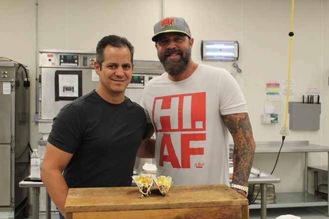 Jason Tilford, left, and Mike Johnson, right, pose for a photo in front of their new creation: the bacon cheeseburger taco. - COURTESY OF MISSION TACO JOINT