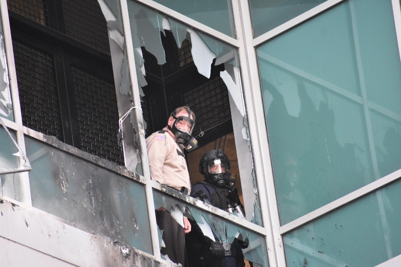A St. Louis Sheriff's deputy and police SWAT supervisor look out of shattered window on February 6, 2021, at the City Justice Center. - DOYLE MURPHY