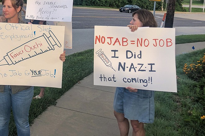 An anti-vaccine protester outside Mercy Hospital in St. Louis holds up a sign comparing a vaccine mandate for employees to Nazi policies. - VICTOR STEFANESCU