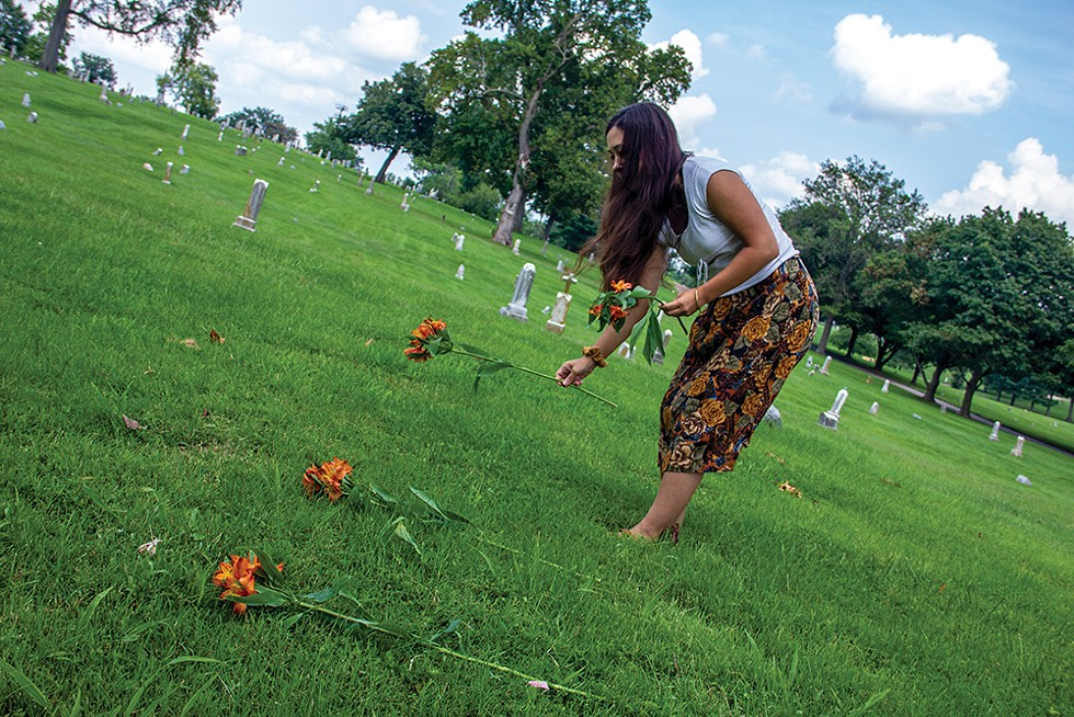 """Janna Añonuevo Langholz places flowers at the graves of tribal members imported for the 1904 World's Fair's """"Philippine Village."""""""