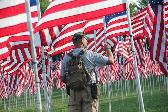 James Presson looks through the field of flags for the members of the unit he served with in Afghanistan. - DANNY WICENTOWSKI