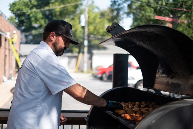 Chris Armstrong is thrilled to be tending to the smoker and grill at Navin's BBQ. - PHUONG BUI