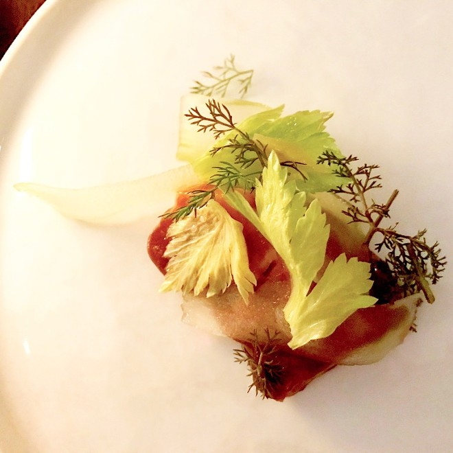 Celery Root / Coffee / 40 day Allium — Celery root bulbs baked in spent coffee grinds from Sump Coffee topped with a sauce made from different alliums cooked for 40 days; stuck to the bulb is shaved celery, celery leaves and fennel fronds. - SARA GRAHAM
