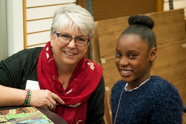 Jeane Vogel meets with Divine Robinson, a fourth grader at Washington Elementary, on interview night. - COURTESY OF THE BLOOMING ARTISTS PROJECT